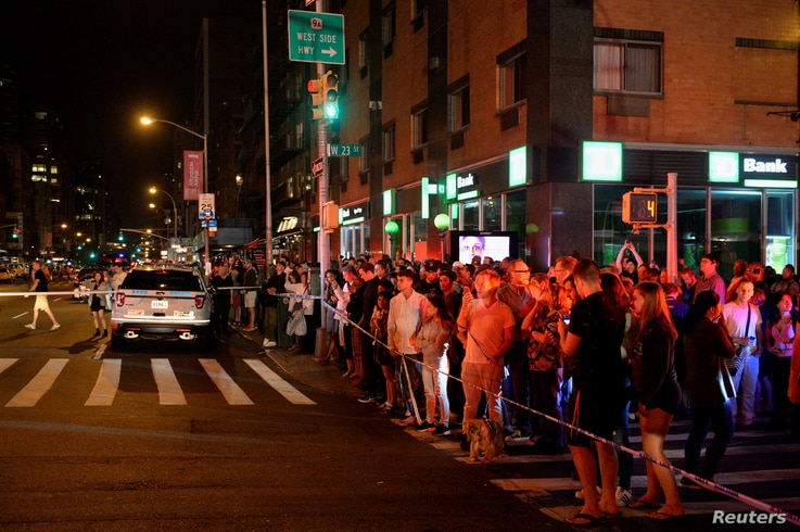 Onlookers stand behind a police cordon near the site of an explosion in the Chelsea neighborhood of Manhattan, New York, Sept. 17, 2016.