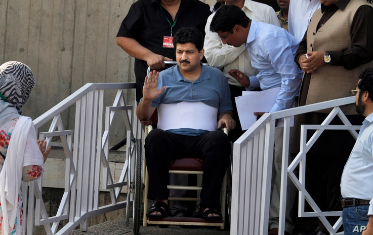 FILE - Pakistani journalist Hamid Mir, who was injured in an attack by unknown assailants on April 19, 2014, waves as he leaves the Supreme Court in Islamabad, Pakistan, May 19, 2014. He appeared at the court as part of an inquiry into the attack aga...
