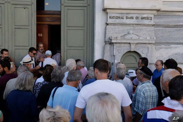 The first customers, most of them pensioners, stand in a queue to enter a branch at National Bank of Greece headquarters in Athens, Monday, July 20, 2015. Greek banks reopen on Monday morning, but many restrictions on transactions, including cash wit...
