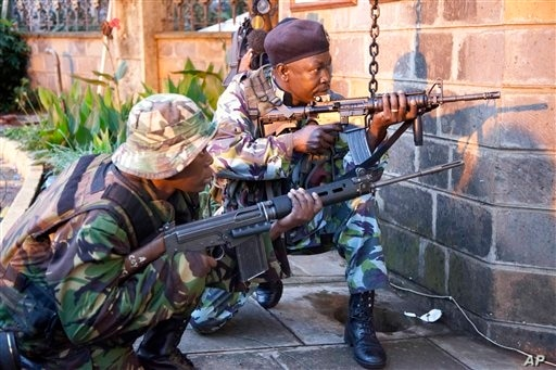 "Kenya security personnel take cover outside the Westgate Mall after shooting started inside the mall early Monday morning, Sept. 23, 2013. Kenya's military launched a major operation at the upscale Nairobi mall and said it had rescued ""most"" of the h"