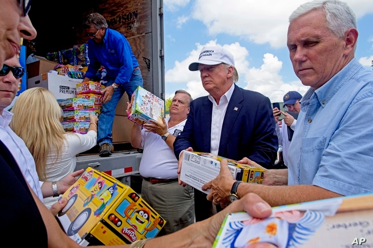 Republican presidential candidate Donald Trump and his running mate, Indiana Gov. Mike Pence, right, help to unload supplies for flood victims during a tour of the flood damaged area in Gonzales, Louisiana, Aug. 19, 2016.