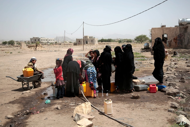 FILE - People fill buckets with water from a well that is alleged to be contaminated water with the bacterium Vibrio cholera, on the outskirts of Sanaa, Yemen, Jul. 12, 2017.