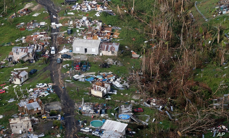FILE - In this Sept. 28, 2017, photo, damaged and destroyed homes are seen in the aftermath of Hurricane Maria in Toa Alta, Puerto Rico. If you think this has been a wild and costly year for weather disasters, federal meteorologists say you are right