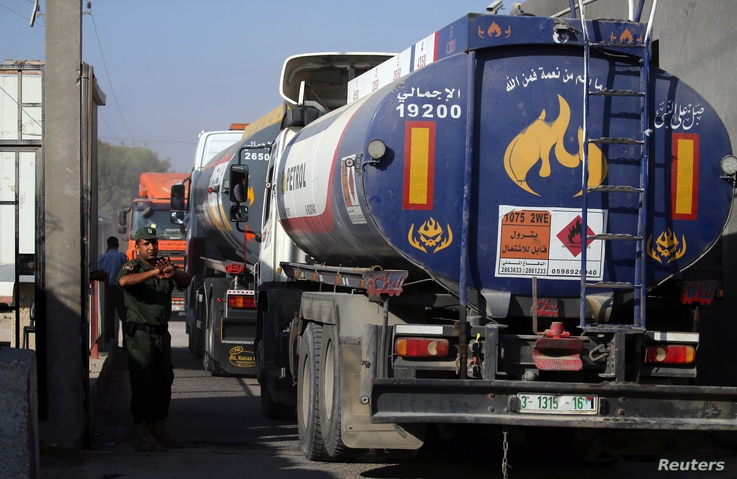 A member of Palestinian security forces gestures as a fuel tanker arrives at Kerem Shalom crossing in Rafah in the southern Gaza Strip, Aug. 15, 2018.