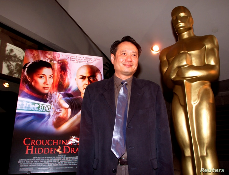 "FILE - Director Ang Lee stands next to the movie poster for his Academy Award-nominated film, ""Crouching Tiger, Hidden Dragon,"" at the Academy of Motion Pictures of Arts and Sciences in Beverly Hills, March 23, 2001."