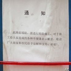 Chinese notice hangs on a metal barrier of the construction site on Wangfujing Street in Beijing.