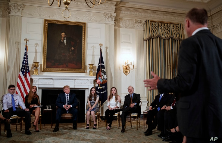 Marjory Stoneman Douglas High School students and parents and President Donald Trump look to Mark Barden, standing right, of Sandy Hook Promise and father of Sandy Hook shooting victim Daniel Barden, as he speaks during a session with high school stu...