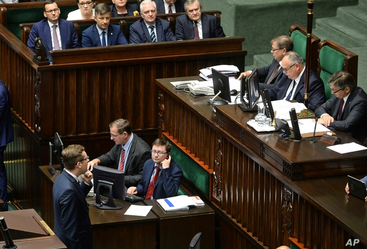 Polish Prime Minister Mateusz Morawiecki, upper left, looks on as a lawmaker for Poland's extreme right, Robert Winnicki, lower left, blocks the parliament's podium in a failed attempt to obstruct a vote on canceling penal provisions in Poland's Holo...
