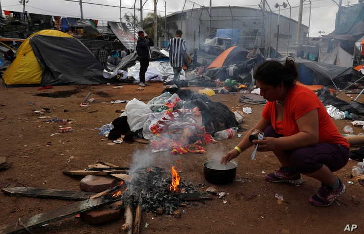 A woman makes instant coffee over a campfire a day beside belongings soaked in rains which continued overnight, inside the Benito Juarez sports complex in Tijuana, Mexico, Nov. 30, 2018.