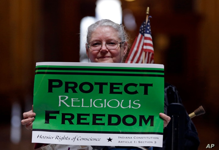 FILE - Condy Holmes of Mechanicsburg, Ind. holds a sign a rally at the Statehouse in Indianapolis, Indiana.