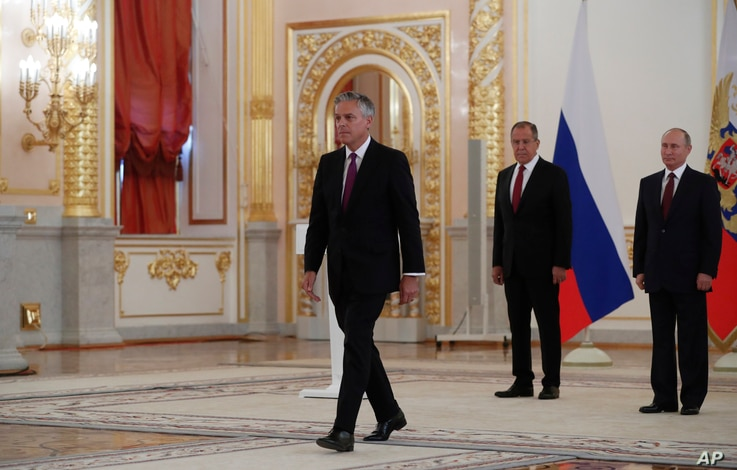U.S. Ambassador Jon Huntsman walks after presenting credentials to Russian President Vladimir Putin, right, during a ceremony in the Kremlin in Moscow, Russia, on Tuesday, Oct. 3, 2017.