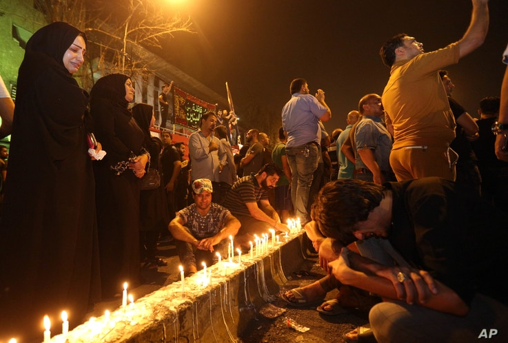 Iraqi women grieve as people light candles at the scene of a massive car bomb attack in Karada, a busy shopping district where people were shopping for the upcoming Eid al-Fitr holiday, in the center of Baghdad, Iraq, Monday, July 4, 2016.