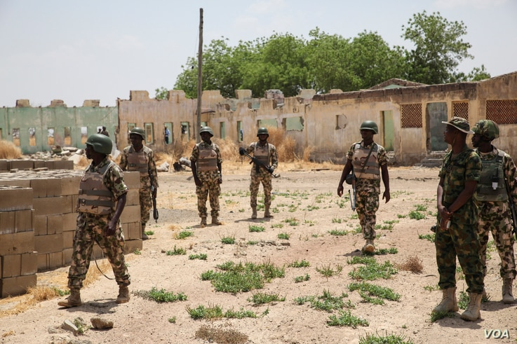 Soldiers walk among the ruins of the Government Secondary School in Chibok, Nigeria, March 25, 2016.