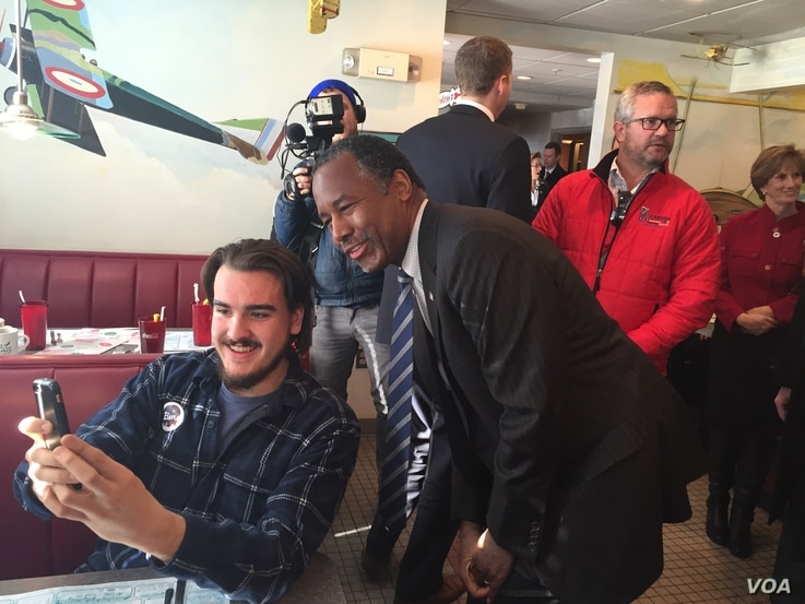 Republican presidential candidate Ben Carson takes a photo with a diner at the Airport Diner in Manchester, New Hampshire, Feb. 7, 2016.