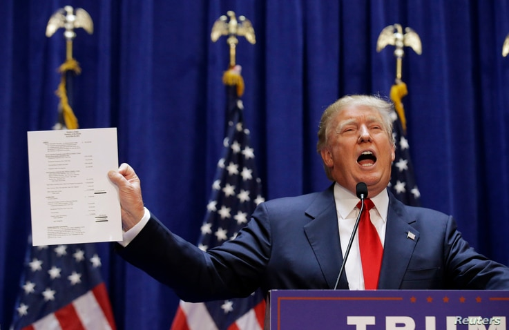 U.S. Republican presidential candidate, real estate mogul and TV personality Donald Trump holds up his financial statement showing his net worth as he formally announces his campaign for the 2016 Republican presidential nomination in New York, June 1...