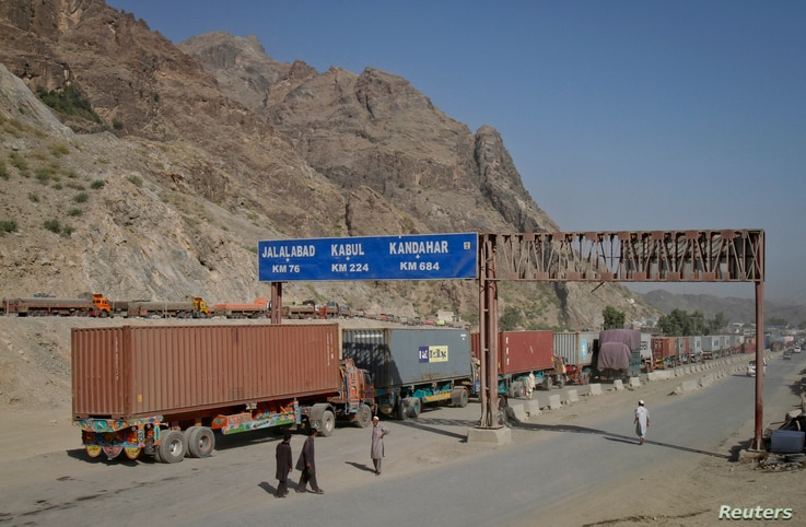 FILE - Men walk near a road sign showing the distance to cities in Afghanistan, as trucks drive past in the northwest town of Torkham, at the border crossing to Pakistan, July 4, 2012.
