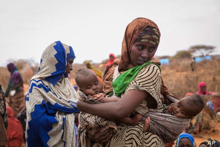 FILE - Basherow Hassen, a mother of four, waits for food aid with her twin children in the Warder district in the Somali region of Ethiopia, Jan. 28 2017.