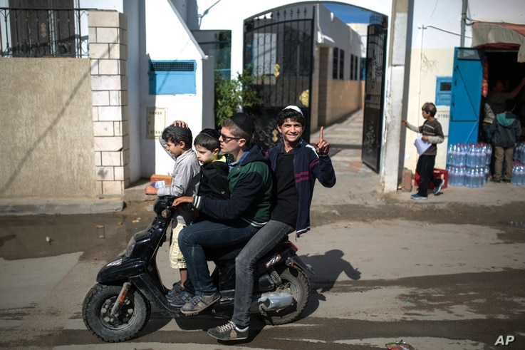 A boy gestures to the camera as he and his relatives leave school at Hara Kbira, the main Jewish neighborhood on the island of Djerba, southern Tunisia, Oct. 30, 2015..