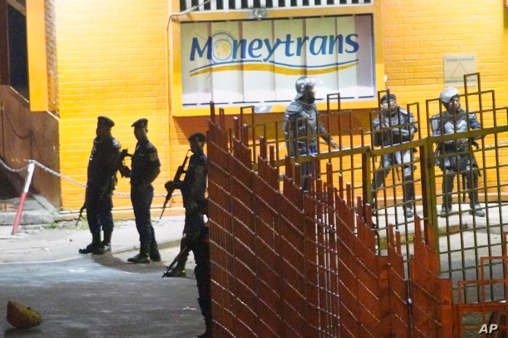 Congolese riot police take position around the electoral commission building at night in Kinshasa, Congo, Jan. 8, 2019.