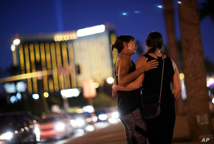 Madisen Silva, right, and Samantha Werner embrace at a makeshift memorial for victims of a mass shooting in Las Vegas, Oct. 6, 2017.