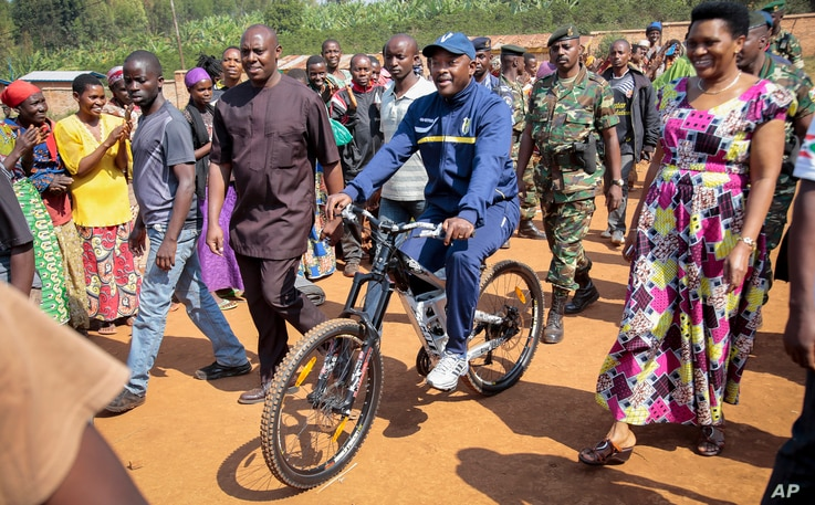 President Pierre Nkurunziza arrives riding a bicycle, accompanied by first lady Denise Bucumi Nkurunziza, right, to cast his vote for the presidential election, in Ngozi, Burundi, July 21, 2015.