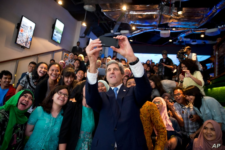 Secretary of State John Kerry takes a selfie with a group of students before delivering a speech on climate change on Sunday, Feb. 16, 2014, in Jakarta.