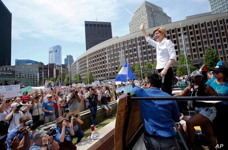 Sen. Elizabeth Warren, D-Mass., waves to the crowd from the back of a pickup truck prior to speaking at the Rally Against Separation, June 30, 2018, in Boston.