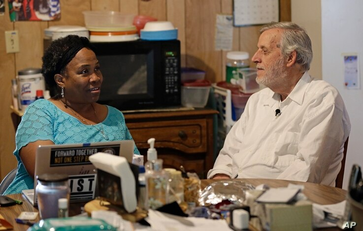 FILE - Civil rights attorney Al McSurely and his wife, O'Linda Williams, sit together in the kitchen of their home in Carthage, N.C., June 6, 2018.