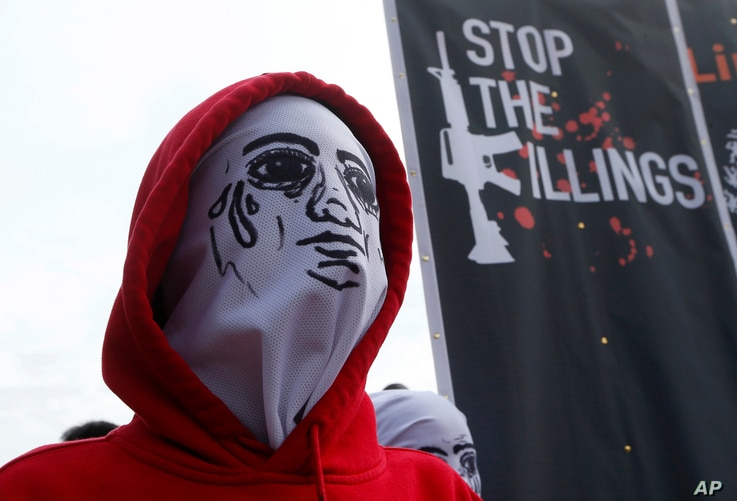 A masked protester stands next to a banner condemning President Rodrigo Duterte's war on drugs, during a rally to coincide with his third State of the Nation Address, July 23, 2018, in Quezon city, metropolitan Manila, Philippines.