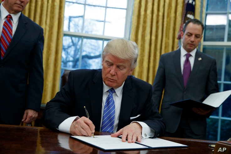 President Donald Trump signs an executive order to withdraw the U.S. from the 12-nation Trans-Pacific Partnership trade pact agreed to under the Obama administration, Jan. 23, 2017, in the Oval Office of the White House.