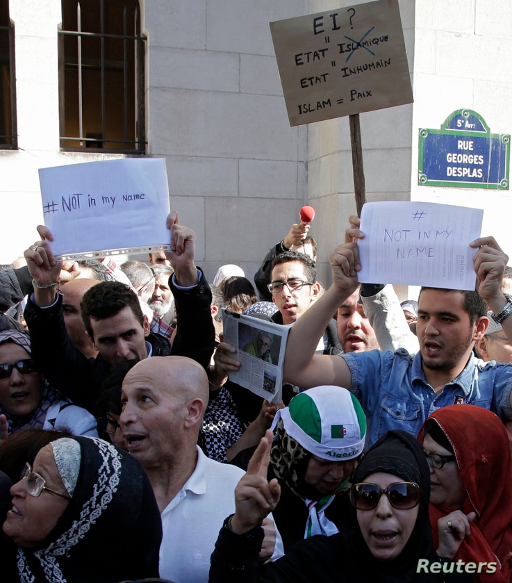 "Muslims holding signs saying ""not in my name"" gather in front of the Paris Mosque after Friday prayers Sept. 26, 2014 to pay tribute to Herve Gourdel, a French mountain guide who was beheaded by an Algerian Islamist group, and to protest extremist ta..."