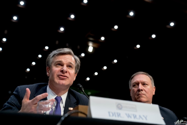 FBI Director Christopher Wray, accompanied by CIA Director Mike Pompeo, right, speaks at a Senate Select Committee on Intelligence hearing on worldwide threats, in Washington, Feb. 13, 2018.