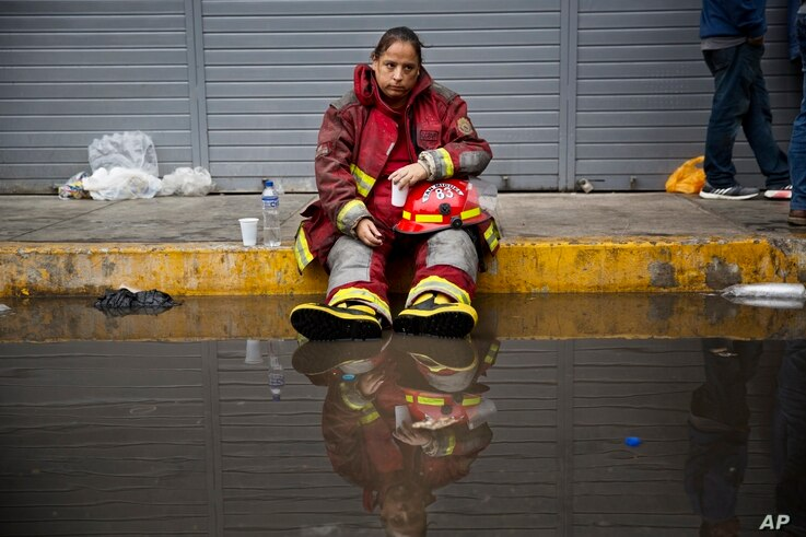In this June 23, 2017, photo, exhausted firefighter Julia Alegre Smith rests after battling a warehouse fire in Lima, Peru.