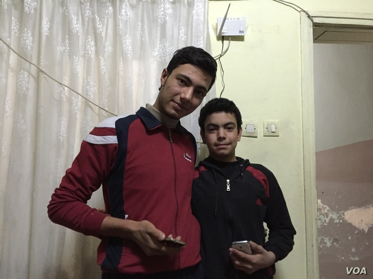 Syrian refugees Ahmet, 19, and his 15 year-old brother Muhammet pose with their smartphones earlier this year in the apartment they share with their family in Gaziantep, Turkey.