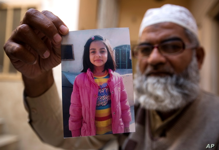 Mohammed Amin shows a picture of his seven year-old daughter, Zainab Ansari in Kasur, Pakistan, Jan. 18, 2018.