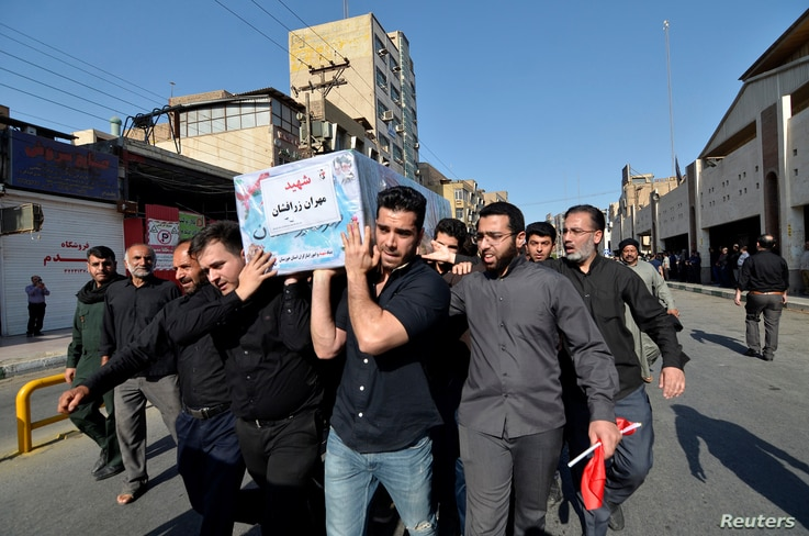 People carry a coffin during a funeral of the victims of assault that killed 25 people, in the streets of the southwestern Iranian city of Ahvaz, Iran Sept. 24, 2018.
