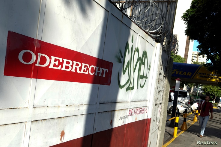 FILE - A man walks past the corporate logo of Odebrecht in a construction site in Caracas, Venezuela, Jan. 26, 2017.