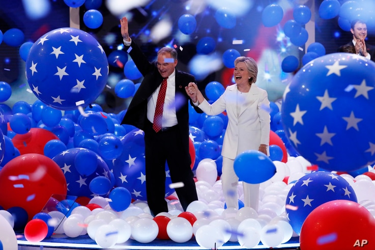 Democratic vice presidential nominee Tim Kaine and Democratic presidential nominee Hillary Clinton walk through the falling balloons during the final day of the Democratic National Convention in Philadelphia, July 28, 2016.