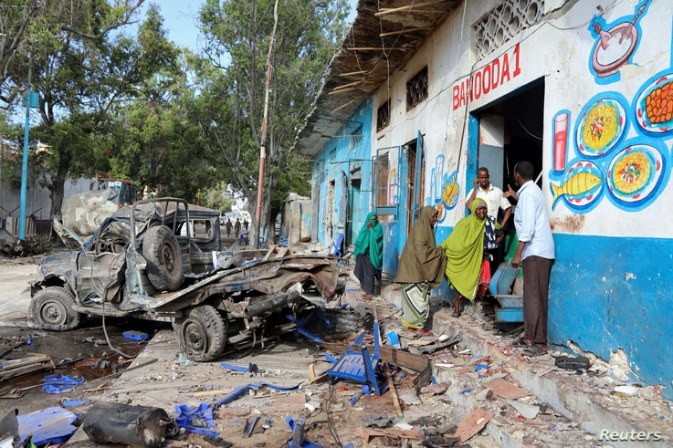 Residents gather at the scene of a suicide car bomb explosion, at the gate of Naso Hablod Two Hotel in Hamarweyne district of Mogadishu, Somalia, Oct. 29, 2017.