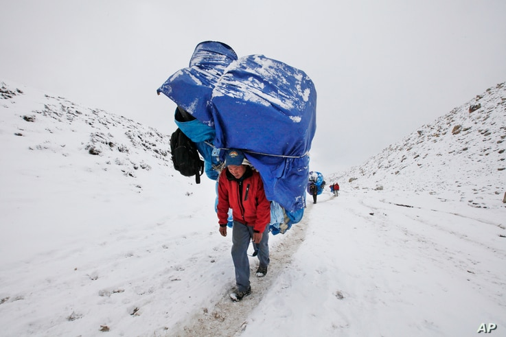 FILE - A porter walks with a massive load towards Everest Base camp near Lobuche, Nepal, March 28, 2016. After two hard years for mountaineers, more than 200 climbers have scaled the daunting mountain in the past 10 days, sending a wave of optimism t...