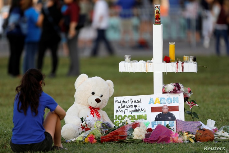 A mourner sits by a cross adorned with pictures of victims, along with flowers and other mementoes, at a memorial two days after the shooting at Marjory Stoneman Douglas High School in Parkland, Florida, Feb. 16, 2018.