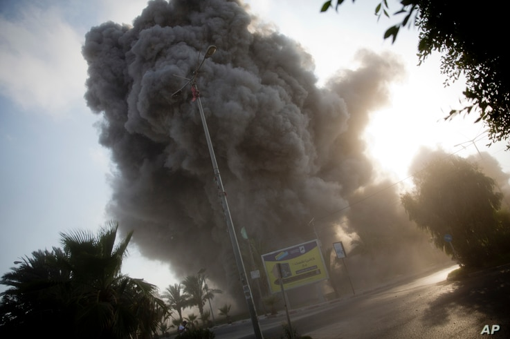 Smoke raises in the background following an Israeli airstrike hits a governmental building in Gaza City , Saturday, July 14, 2018.