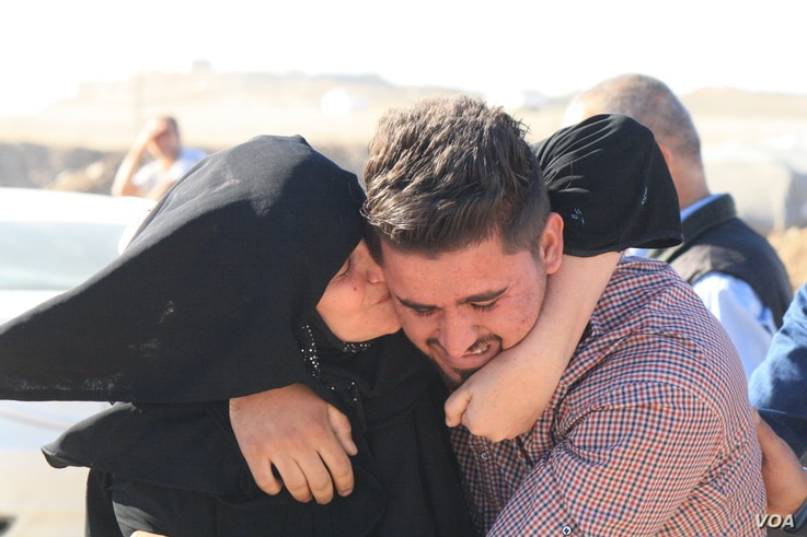 A mother weeps and hugs her son she hadn't seen in the two and a half years he has been trapped in on Nov. 3, 2016, at the Khazir camp in Kurdish Iraq. (H.Murdock/VOA)