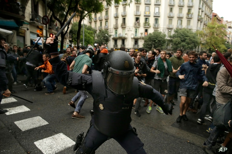 In this Oct. 1, 2017 photo, a Spanish riot police swings a club against would-be voters near a school assigned to be a polling station by the Catalan government in Barcelona, Spain.