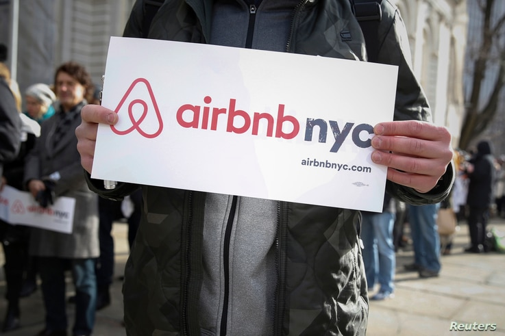 "Supporters of Airbnb stand during a rally before a hearing called ""Short Term Rentals: Stimulating the Economy or Destabilizing Neighborhoods?"" at City Hall in New York, Jan. 20, 2015."