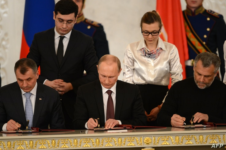 Russia's President Vladimir Putin (C),  Crimean parliament speaker Vladimir Konstantionov (L)  and Alexei Chaly, Sevastopol's new de facto mayor (R), sign a treaty to make Crimea part of Russia in the Kremlin in Moscow on March 18, 2014.
