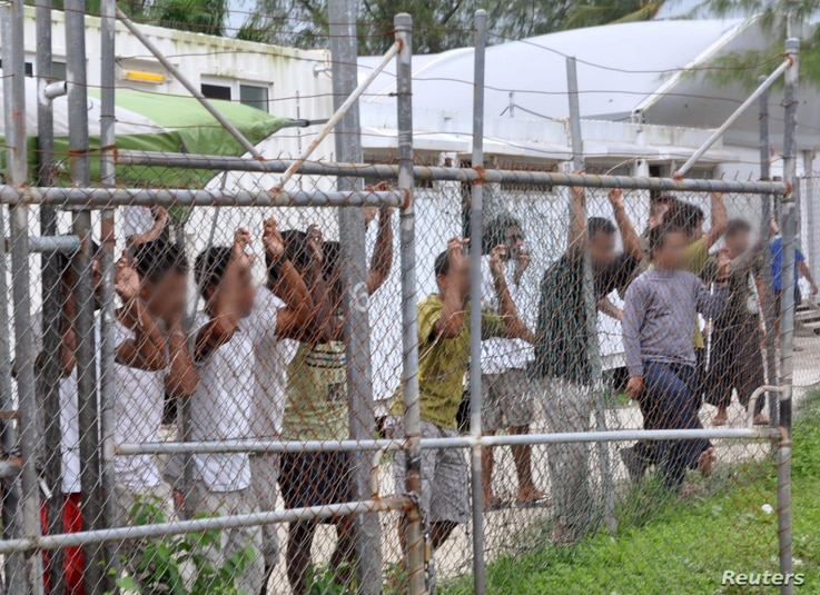 FILE - Asylum-seekers look through a fence at the Manus Island detention center in Papua New Guinea, March 21, 2014.