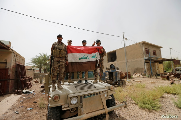 Iraqi army soldiers hold Iraqi flag on a top of a military vehicle in the centre of Fallujah, Iraq, June 18, 2016.