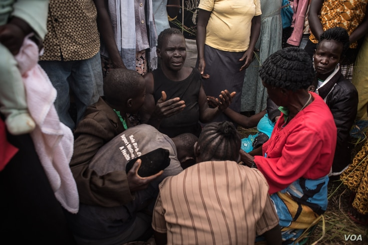 The mother of Duku Evans — who was killed November 3 amid fighting between government troops and rebels in Logo displaced persons camp in Kajo Keji, South Sudan — prays with her hands out during her son's funeral on the Ugandan border, Nov. 5, 20...