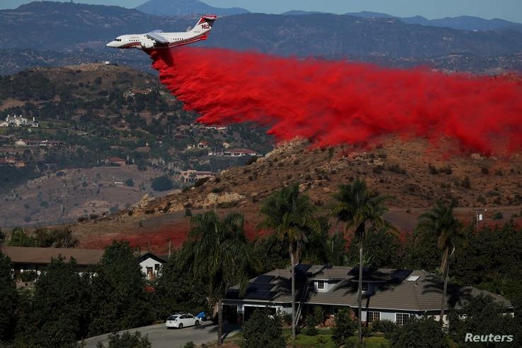 An aircraft drops fire retardant as firefighters take advantage of light winds to attack the Lilac Fire, a fast-moving wildfire in Bonsall, California, Dec. 8, 2017.